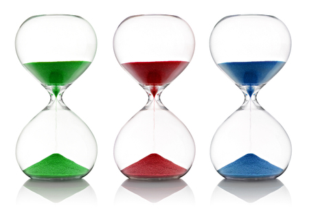 the passing of time: Colored sand, red, green and blue, running through glass hourglasses measuring passing time as they count down to a deadline, isolated on white