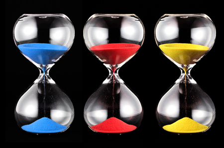passing over: Three hourglasses with colorful sand, blue, red and yellow,running through the glass bulbs measuring the passing time or time remaining to a deadline, over a black background