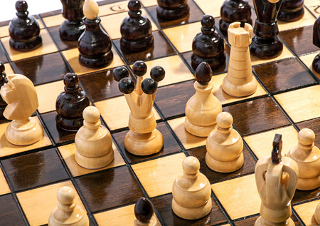 high angle: Close up high angle view of light and dark wooden chess pieces on a board during a game in progress