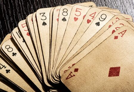 discolored: Overhead view of a fanned deck of old grungy discolored dirty vintage playing cards, conceptual of gambling and casinos