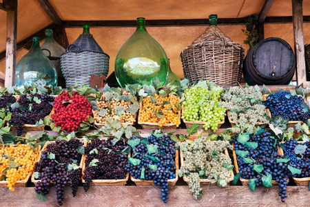 wine making: Display of assorted colored grapes in wicker trays below a shelf of old wine storage bottles in a winery, tavern or market, conceptual of viticulture, agriculture and wine making