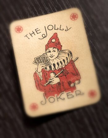 Vintage Joker playing card with a cheerful red jester holding a hand of cards on a black background with selective focus to the face, conceptual of luck and gambling