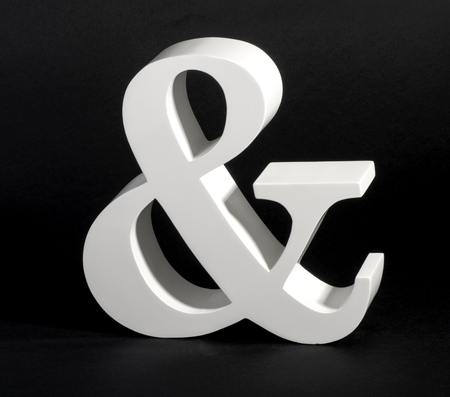 conjunction: Dimensional white Ampersand symbol on a black background, a conjunctive character depicting the word - and - in written or printed text