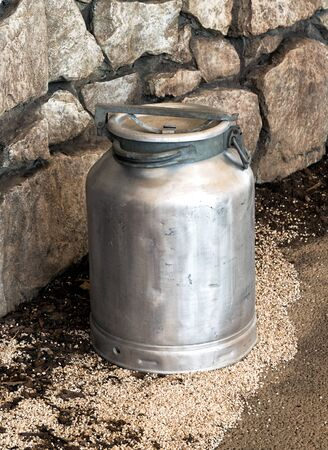 urn: Old vintage metal aluminium milk churn, urn or can used on a dairy farm with its lid in place displayed against a natural rock wall, high angle view