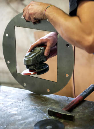 metalworker: Metalworker sanding a metal component with a disc sander smoothing the edges on a square cutout in a circular plate in an industrial workshop of factory Stock Photo