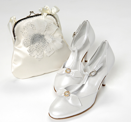 court shoes: Stylish white bridal accessories with a pair of elegant court shoes decorated with bows and a matching handbag displayed over a white background