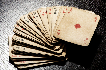 discolored: Deck of grungy dirty discolored old playing cards stacked with an ace of diamonds on top conceptual of a casino, poker and gambling, high angle close up view