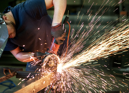metalworker: Metalworker cutting a steel bar using a handheld angle grinder power tool, high angle close up view with flying bright orange sparks