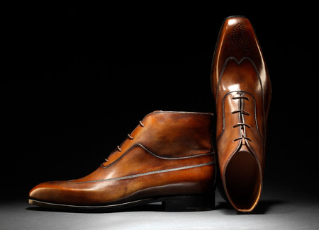Pair of stylish handmade brown leather shoes with laces displayed over a dark background conceptual of original design, quality and craftsmanship, with copyspace