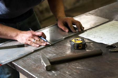 Metalworker marking measurements on a piece of sheet metal using a ruler and tape measure using dimensions from a plan on a sheet of paper on the workbench