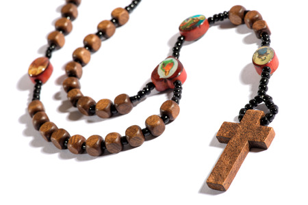 özveri: Roman Catholic rosary for counting off ones prayers on the beads during devotion on a white background with shadow, plain cross and copyspace Stok Fotoğraf