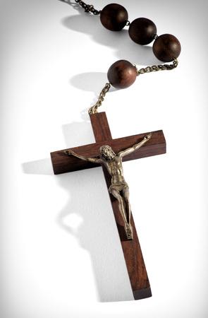 virgen maria: Rosario de madera con un crucifijo adjunta que representa el cuerpo crucificado de Cristo una una cruz de madera llano, vista desde arriba, con especial atenci�n a la cruz sobre un fondo blanco