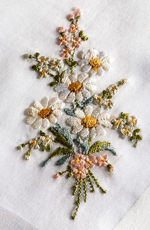 an embroidery: bordados decorativos en un tejido blanco de un ramo de flores de primavera o verano con margaritas blancas en un concepto de artesan�a y costura Foto de archivo