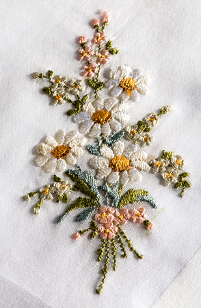 Decorative embroidery on a white textile of a bouquet of flowers with white spring or summer daisies in a handicraft and needlework concept