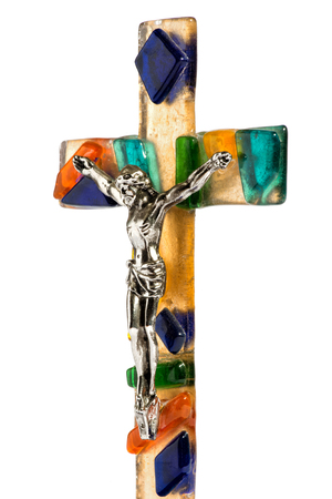 crucified: Close up angled view of the figure of a crucified Christ on a colorful decorative glass cross isolated on a white background Stock Photo