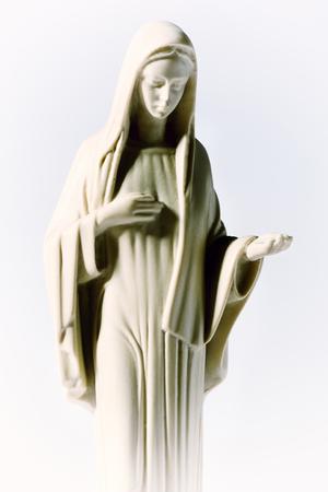 humildad: Estatua de la Virgen Mar�a sobre un fondo blanco que representa la humildad y la caridad como ella extiende su mano vac�a en un concepto religioso del catolicismo romano