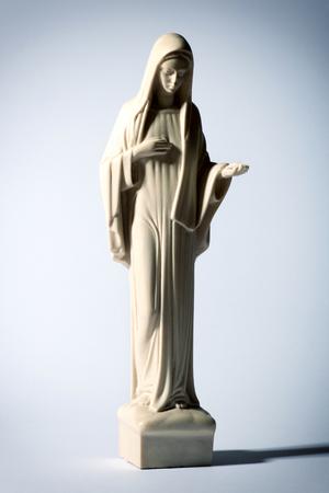 vierge marie: Statue de la Vierge Marie sur un fond gris repr�sentant l'humilit� et de la charit� comme elle �tend sa paume vide dans un concept religieux du catholicisme romain Banque d'images