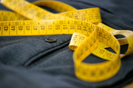 tailor measuring tape: Measuring tape on pants in a tailor workshop, closeup