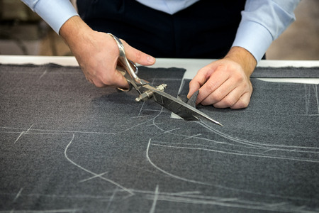 Tailor cutting fabric using large scissors or shears as he follows the chalk markings of the pattern, close up of his hands