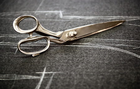 scissors: Tailors scissors lying on fabric marked in chalk with the pattern of the garment in a close up view with copyspace