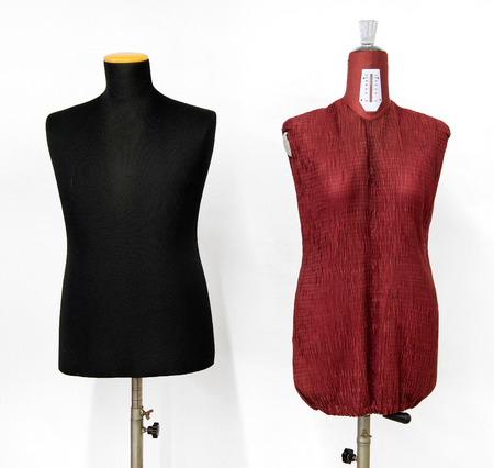 female form: Two vintage mannequins on stands, one black male form and one maroon female form side by side over white Stock Photo