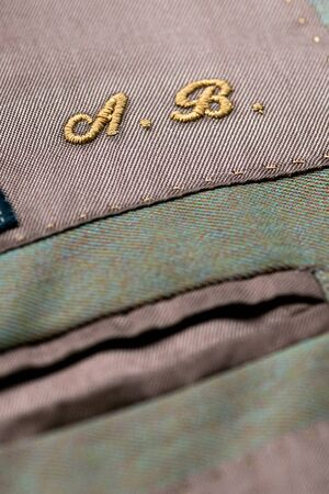 initials: Embroidered initials on clothing with the letters A sand B in gold thread above a pocket, detail of the texture of the cloth