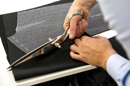 Tailor cutting fabric with shears or scissors following the chalk pattern, close up view of his hands Stock Photo