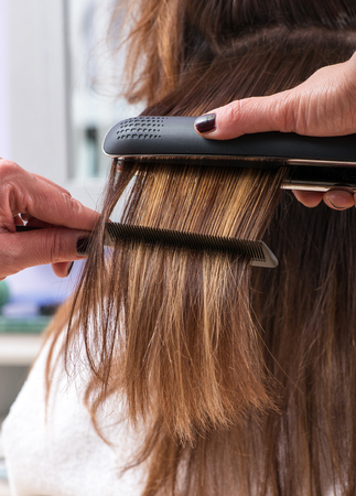 straightener: Hairdresser using a hair straightener on the long brown hair of a female client, close up view of her hands