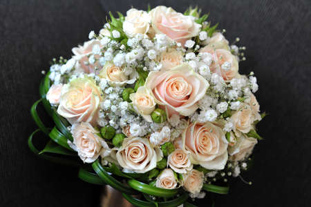 dainty: Pretty bridal bouquet with fresh pink roses in a dainty circular arrangement viewed high angle over a dark background