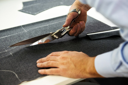 Tailor cutting out the marked pattern on dark fabric with large scissors on the workbench in his shop, close up view of his hands Stock Photo