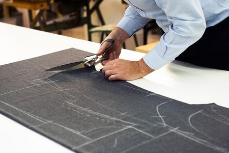 그는 재단사가 분필로하고있다 의류의 패턴을 표시했습니다있는 어두운 직물의 롤을 절단 자신의 가게에서 일하는 재단사, 뷰를 닫습니다 스톡 콘텐츠