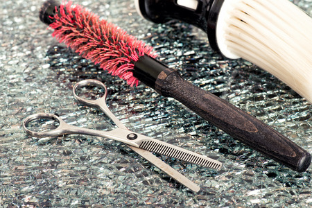 Hairstylists tools lying on a textured counter in the salon with stainless steel scissors and a red hairbrush, close up high angle view