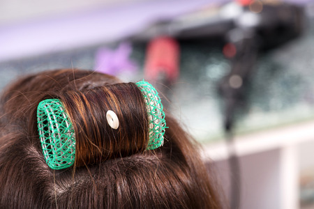 hair curler: Single large green roller or hair curler in brown hair on top of the head of a woman client in a hairdressing salon, close up view Stock Photo