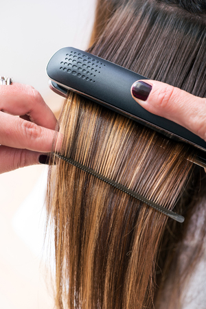 straightener: Hairstylist straightening the long brown hair of a female client using a heated hair straightener, close up view of her hands
