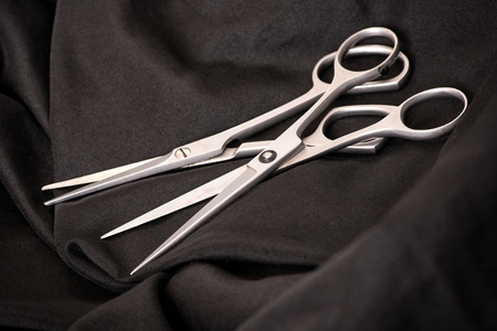 hairstyling: Two pairs of professional stainless steel hairstyling scissors lying together on dark fabric, close up high angle view