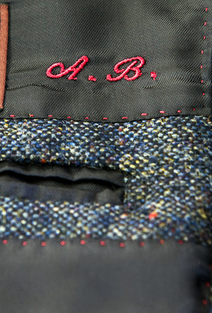 tailored: Embroidered red initials above the pocket on a tailored garment conceptual of bespoke fashion and couture Stock Photo