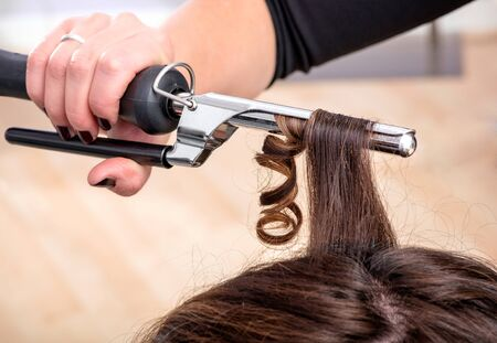ringlets: Hairstylist using a curling iron or tongs to firm ringlets in the long brown hair of a female client in a hairdressing salon, close up view of her hand and the appliance