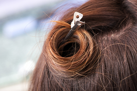 hair stylist: Metal hairpin in brown hair holding it up in a curl in a hairdressing salon so that the stylist can cut it