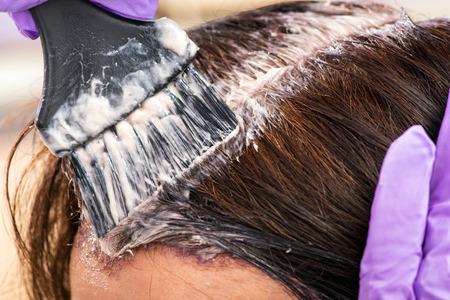 Friseur einen Farbton zu dem braunen Haar einer Kundin in einem Salon Auftragen mit einem Pinsel auftragen, Nahansicht