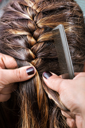braiding: Hairdresser braiding a clients long brown hair plaiting it close to her head as she works in a hairdressing salon, close up view of her hands Stock Photo