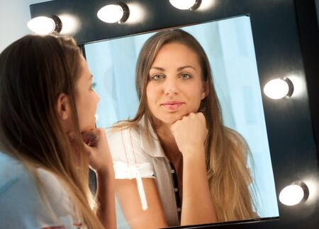 dressing table: Attractive young girl with long brown hair sitting at a dressing table staring into the mirror with a thoughtful expression, focus to her reflection