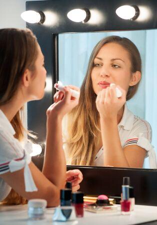 jeune fille: Jolie jeune femme aux longs cheveux bruns assis � une table de toilette appliquer le rouge � l�vres, voir � son reflet dans le miroir dans un concept de beaut� Banque d'images