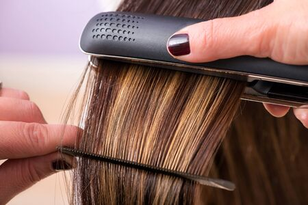 capelli biondi: Hairstylist straightening the long brown hair of a female client using a heated hair straightener