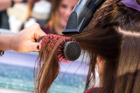 Stylist Bürsten Haar mit einem Haartrockner