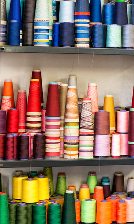 cotton thread: Textile Background Still Life - Shelves Crammed Full of Colorful Cotton Thread Spools in Industrial Size Stock Photo