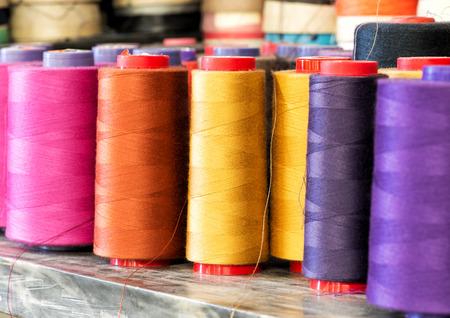 Textile Stillleben - Close Up of Industrial Größe Spulen des Baumwollfaden in lebhaften Farben von Rosa, Orange, Gelb und Lila