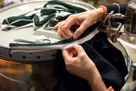 looping: Looping machine operator working in a knitwear factory Stock Photo