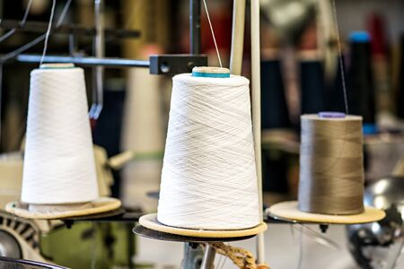 close knit: Close Up of Spools of Cotton Thread Threaded on Industrial Sewing Machine in Knit Wear Factory - Textile Still Life Stock Photo