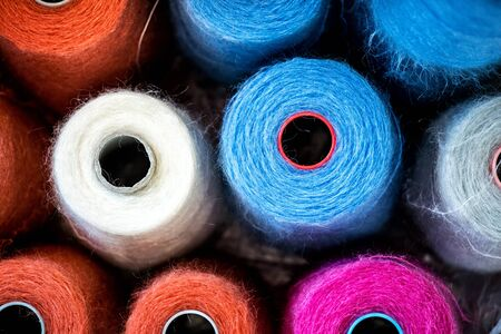 Colorful reels or spools of cotton thread for use in the knitwear and garment industry viewed from above, full frame background