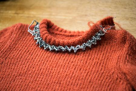 knitwear: Working on woolen sweater collar in a knitwear factory